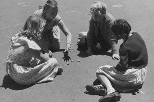 Photo from Museum Victoria and shows four young girls sitting in a circle on an asphalt surface, playing with sheep knucklebones in a government school playground in 1954.