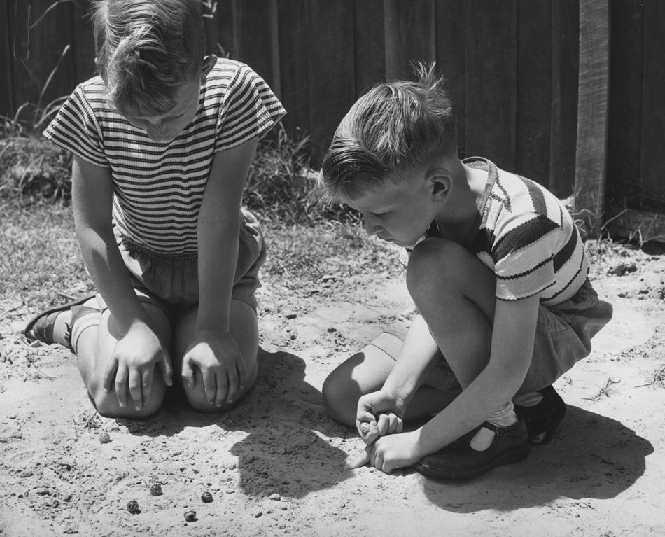 Photo from Museum Victoria and is from 1954. There were several different games of marbles, you could play 'keeps', which meant the winner kept the loser's marble, or not keeps, just a friendly game.