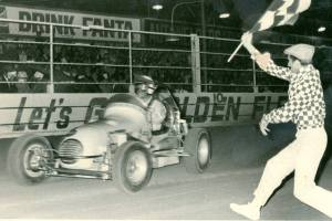 Photo thanks to 'Down Memory Lane With Noel O'Connor'. Driver Bob Wente takes the chequered flag at Rowley Park Speedway. And is that a young Glen Dix